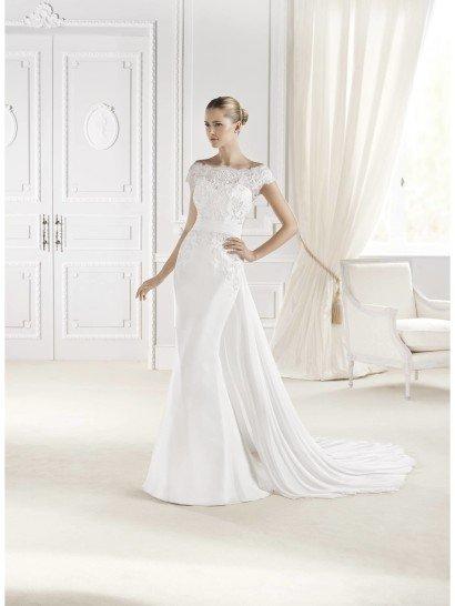Свадебное платье со съемным шлейфом покоряет своим сложным и экстравагантным кроем.  Силуэт русалка и женственные формы лифа дополнены потрясающим шлейфом, ниспадающим сзади от линии талии, подчеркнутой широким поясом.  В качестве декора использовано кружево, полностью покрывающее лиф и элегантно спускающееся до уровня бедер.