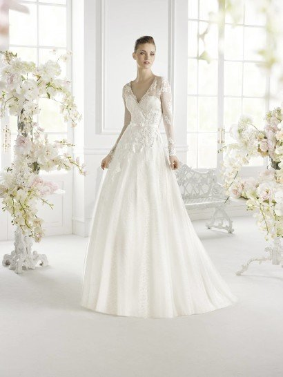 Закрытое свадебное платье со скульптурной четкостью линий. V-образный вырез декольте подчеркивает хрупкость и изящество невесты, такой же эффект производит и сочетание небольшого пояса на талии с А-силуэтом объемной юбки.  Небольшой бант на поясе служит декором. Кроме того, верх платья оформлен с помощью кружевных аппликаций и полупрозрачной ажурной ткани с мелким рисунком.  Свадебное платье из коллекции Avenue Diagonal 2015 / Pronovias Fashion Group /
