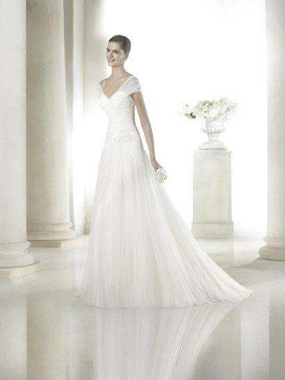 Свадебное недорогое прямое платье в сдержанном классическом стиле идеально впишется в атмосферу традиционного торжества.  Открытое декольте V-образной формы оформлено легкой просвечивающей тканью с нежными драпировками на плечах.  Драпировки ткани декорируют и область талии.  Они гармонично сочетаются с ниспадающей юбкой со шлейфом среднего размера.  Завершающим штрихом служит ассиметрично расположенная аппликация из кружев на поясе.  Свадебное платье San Patrick от Pronovias Fashion Group