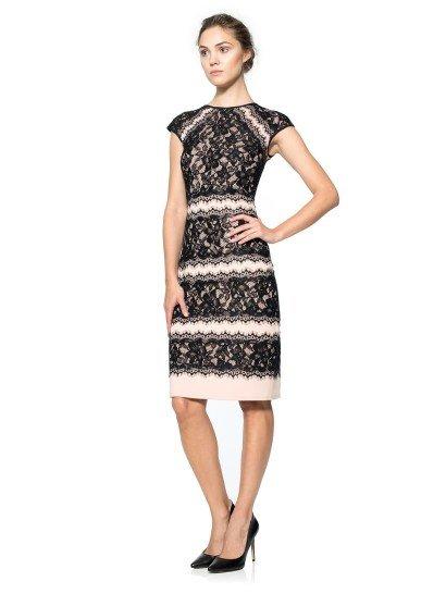 Вечернее платье длиной до колена с закрытым верхом и коротким рукавом выразительно декорировано контрастной кружевной тканью. Черный ажурный материал выделяется на пудрово-бежевой ткани, приобретая богатую текстуру.  Стильный прямой крой вечернего платья в сочетании с нежной и романтичной отделкой кружевом позволяет создать женственный и соблазнительный образ для праздничного мероприятия.