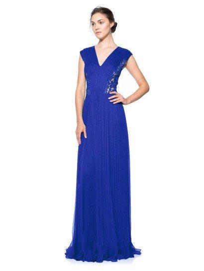 Элегантное вечернее платье длиной в пол выделяется насыщенным синим цветом ткани и нежной отделкой.   Прямой крой с V-образным вырезом идеален для создания женственного силуэта и подчеркивает область декольте.  Мелкая плиссировка ткани придает вечернему платью оригинальную текстуру, которую красиво дополняют прозрачные кружевные вставки по бокам.   Кроме того, такой декор визуально вытягивает фигуру.