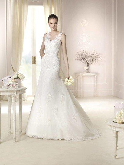 Идеальный выбор для невесты, предпочитающей классические линии и акцент на женственность, это свадебное платье очерчивает силуэт невесты облегающим кроем «русалка» и придает ему изысканность объемным шлейфом.  Отделкой служит кружево, из которого выполнены широкие бретели и которым покрыто все свадебное платье.  На лифе и в области талии фактурный декор расположен плотно, а на юбке ограничен аппликациями.