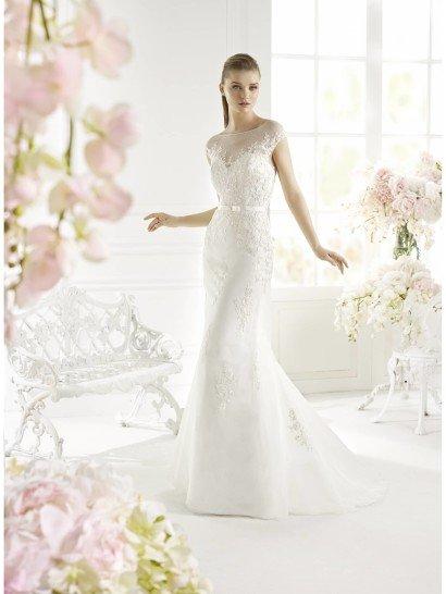 Изысканное недорогоесвадебное платье очерчивает фигуру прямым кроем.  Главным акцентом в силуэте становится небольшой пояс, выделяющий талию невесты.  Декольте в форме сердечка скрыто полупрозрачной тканью, образующей небольшой рукав и вырез лодочкой. Особенную привлекательность такому решению придает текстура ткани с мелким рисунком.  Многослойная юбка украшена кружевными аппликациями и образует сзади небольшой шлейф, который будет элегантно смотреться при любом движении невесты.