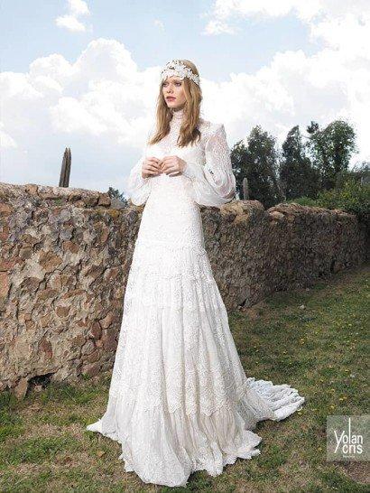 Закрытое свадебное платье с длинным рукавом выполнено в характерном богемном стиле. Прямой силуэт струится по фигуре, не делая акцентов.  Многоуровневая юбка сзади спускается небольшим шлейфом.  Особенно привлекает внимание отделка – плотное кружево с цветочным рисунком, покрывающее платье от высокого воротника до края шлейфа.  Из него же выполнены широкие манжеты на длинных рукавах из ажурной полупрозрачной ткани.  Свадебные платья Yolan Crisэксклюзивно представлены в салоне Виктория  Примерка платьев Yolan Cris -платная