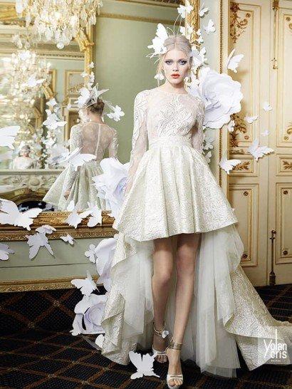 [vc_row][vc_column][vc_column_text]Закрытое свадебное платье задерживает взгляд кроем юбки с укороченным подолом спереди и многослойным шлейфом сзади. Верх свадебного платья с длинным рукавом и высоким вырезом выполнен из полупрозрачной ткани с кружевными аппликациями и прозрачной вставкой на спине.  Юбка А-силуэта сшита из плотной глянцевой ткани серебристого оттенка с богатой текстурой, а под ней располагается несколько пышных слоев белого матового тюльмарина.  Свадебные платья Yolan Crisэксклюзивно представлены в салоне Виктория  Примерка платьев Yolan Cris -платная[/vc_column_text][/vc_column][/vc_row]