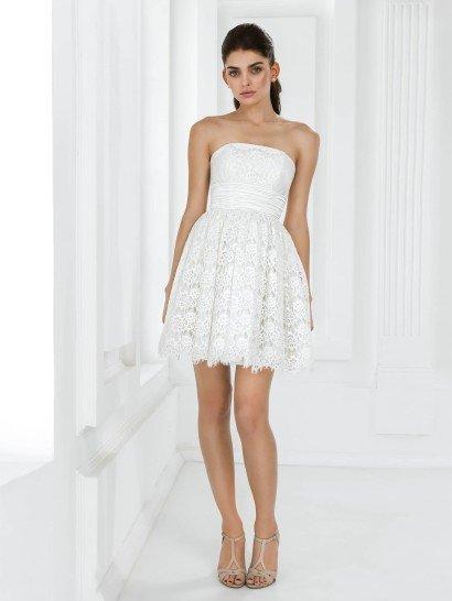 Короткоесвадебное платье с пышной юбкой длиной до середины бедра создает оригинальный и нежный образ юной невесты.  Прямой крой лифа придает линии плеч и области декольте изящество, а талия выделена широким поясом с фактурными драпировками.  Короткая юбка выполнена из нескольких слоев ткани.  Верхний выполнен из кружева с плотным узором и образует ажурный край подола.  Такое же кружево декорирует и лиф свадебного платья.
