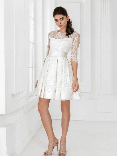Короткоесвадебное платье с юбкой до середины бедра задает романтичную и торжественную атмосферу.  Такое впечатление создают кружевная отделка платья, образующая верх с вырезом-лодочкой и рукавом длиной в три четверти, и широкий пояс из глянцевого атласа, охватывающий талию.  Декорированная кружевной тканью атласная юбка скроена с драпировками ткани, которые подчеркивают настроение образа.