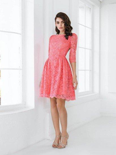 Элегантное платье для выпускного вечера не смотрится слишком сдержанным, несмотря на закрытый крой, благодаря романтичной фактуре кружева, покрывающего платье полностью.  Рукав длиной в три четверти и вырез лодочкой придают силуэту особое изящество.  Объемная юбка длиной чуть выше колена также декорирована кружевом, которое чуть длиннее, чем плотная ткань основы, отчего по краю подола образуется фигурная полоса.  Отлично подойдет для празднования выпускного вечера!