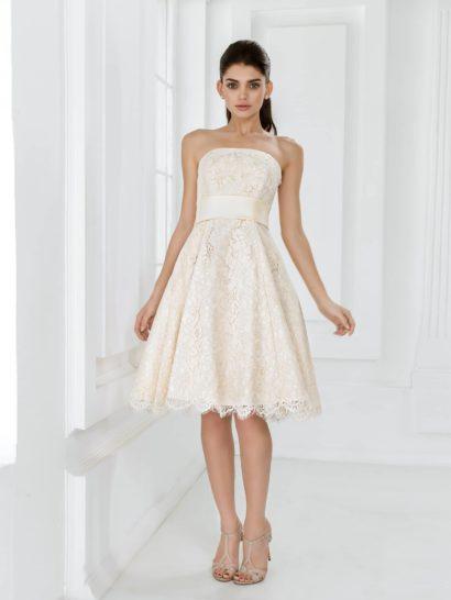 Открытое свадебное платье покоряет своим теплым оттенком слоновой кости.  Прямой вырез декольте хорошо сочетается с широким атласным поясом, выделяющим талию невесты, и женственной пышной юбкой А-силуэта.  В качестве отделки использовано нежное кружево в тон основной ткани, покрывающее цветочным узором весь наряд полностью и образующее полупрозрачный фигурный срез подола на объемной юбке длиной до колена.