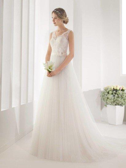 Элегантное свадебное платье с V-образным декольте создает трогательный образ с помощью полупрозрачности тюльмарина и нежности кружева, покрывающего верх платья и образующего симметричные бретели с ажурным краем.  Сзади юбка заканчивается небольшим шлейфом.  На естественной линии талии находится узкий пояс из плотной ткани белого цвета, украшенный ассиметричным цветком из ткани со стразами.