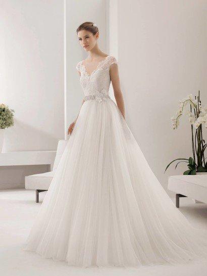 Лаконичное свадебное платье А-силуэта воплощает классический, женственный стиль.  Закрытый верх с небольшим рукавом и вырезом лодочкой смотрится менее строго из-за использования полупрозрачного кружева в качестве ткани.  Объемная юбка из тюльмарина выглядит легкой и ниспадает мягкими складками.  Талию невесты очерчивает узкий пояс с искусственным цветком из ткани, ассиметрично расположенным сбоку.
