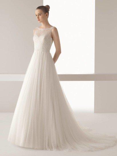 Свадебное платье прямого силуэта с оригинальным кроем юбки и красивым декором верха.  Открытый лиф с вырезом лодочкой выполнен из полупрозрачной ткани, полностью расшитой бисером до линии талии.  Под тканью – более плотный лиф в форме сердечка с глубоким вырезом на спине.  Юбка спускается от талии множеством мелких складок полупрозрачного тюльмарина.  Сзади фатин ниспадает красивым шлейфом в несколько слоев ткани.