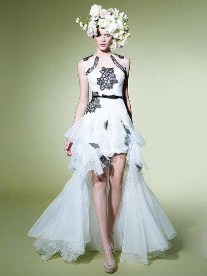 Экстравагантное вечернее платье сочетает в себе сразу несколько контрастных решений: это белая ткань основы и черное кружево декора, а также сдержанный верх с высоким вырезом и необычная юбка с укороченным подолом, выполненная из нескольких слоев полупрозрачной ткани.  Талию охватывает узкий черный пояс с маленьким бантом в центре.  Лиф украшен крупной цветочной аппликацией и симметричными кружевными вставками на плечах.  Вечерниеплатья Yolan Crisэксклюзивно представлены в салоне Виктория  Примерка платьев Yolan Cris -платная