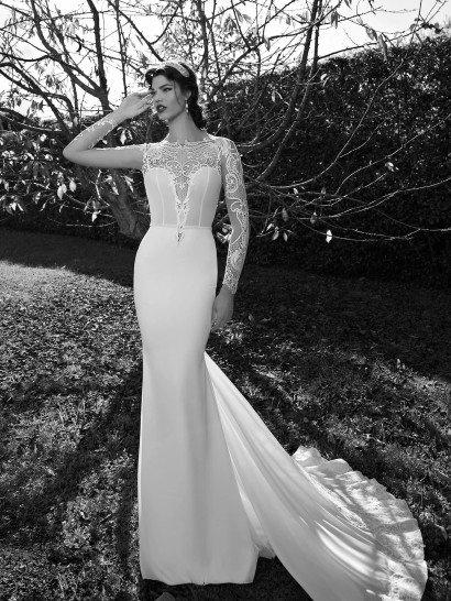 Изысканное свадебное платье облегает фигуру невесты тончайшим шелком.  Сзади, на уровне середины бедер, легкая ткань образует воздушные складки, переходя в стильный шлейф, украшенный по краю широкой полосой плотного кружева.  Кружевной узор декорирует и глубокий V-образный вырез декольте, обнажающий кожу до линии талии, и длинные рукава прямого кроя, полностью скрывающие руки.    Свадебные платьяBerta Bridalэксклюзивно представлены в салоне Виктория  Примерка платьев Berta Bridal -платная