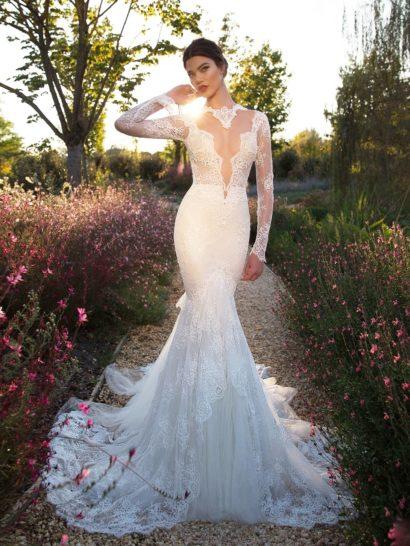 Эксклюзивное свадебное платье приковывает к себе все взгляды – глубокое V-образное декольте, спускающееся до талии и оформленное кружевом, в сочетании с облегающим силуэтом, ниже линии коленей обретающим объем и переходящим в роскошный шлейф, не позволяет сохранять равнодушие.  Создаваемый платьем образ не только соблазнительный, но и романтичный – модель по всей длине декорирована кружевом с нежным рисунком.  Свадебные платьяBerta Bridalэксклюзивно представлены в салоне Виктория  Примерка платьев Berta Bridal —платная