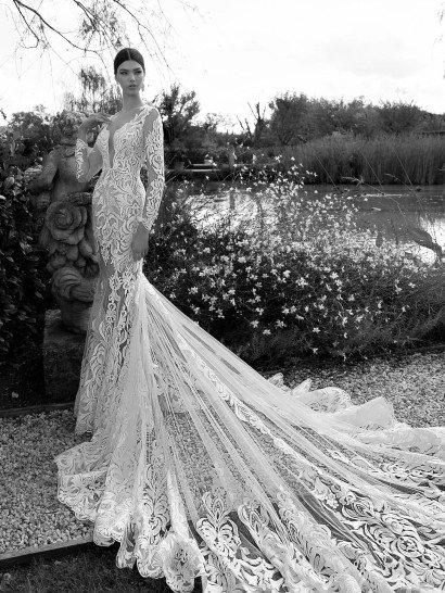 Потрясающее свадебное платье кажется полупрозрачным благодаря ткани основы в тон кожи.  Крупный абстрактный узор ажурной ткани, покрывающий платье полностью, становится от этого еще выразительнее.  Одной из самых броских деталей образа является шлейф, начинающийся сзади на уровне коленей и расходящийся широким прозрачным полукругом далеко за невестой.  Наконец, стоит отметить декольте – глубокий вырез, доходящий почти до линии талии, выглядит сногсшибательно.  Свадебные платьяBerta Bridalэксклюзивно представлены в салоне Виктория  Примерка платьев Berta Bridal -платная