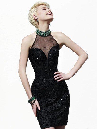 Короткое коктейльноеплатье идеально облегает фигуру силуэтом «футляр».  Черный цвет ткани придает очертаниям особое изящество, а полупрозрачная вставка делает открытое декольте сердечком сдержаннее.  Платье декорируют швы и вышивка из сверкающего бисера, придающая черной ткани выразительную фактуру по всей длине.  Дополнительным украшением становится высокий воротник, полностью покрытый вышивкой с крупными зелеными стразами.