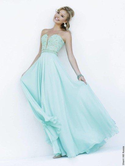 Вечернее платье пастельного оттенка зеленого идеально подчеркивает фигуру глубоким вырезом декольте, дополненным полупрозрачной вставкой в тон кожи.  Лиф покрыт фактурной вышивкой, а линию талии помогает акцентировать отделка из бисера, располагающаяся горизонтальной полосой.  Элегантная юбка прямого кроя спускается объемными волнами до самого пола, красиво завершая торжественный образ для выпускного вечера.