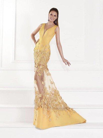 Облегающее вечернее платье выполнено в оригинальном пастельном оттенке желтого.  Соблазнительное глубокое декольте в форме сердца оформлено полупрозрачной вставкой.  Ниже естественной линии талии платье покрывает отделка в виде фактурных цветов из плотной желтой ткани, которые спускаются по прозрачной вставке на середине юбки до самого нижнего края подола, сзади переходящего в небольшой шлейф.