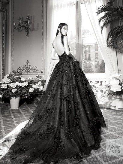 Роскошное вечернее платье выполнено в драматичном черном цвете.  Облегающий верх декорирован кружевом, а сзади украшением образа становится глубокий округлый вырез, открывающий спину.  Многослойная пышная юбка с выразительным шлейфом сзади декорирована объемными цветами из плотной черной ткани, нашитыми на полупрозрачный верхний слой вместе со стразами и пайетками.