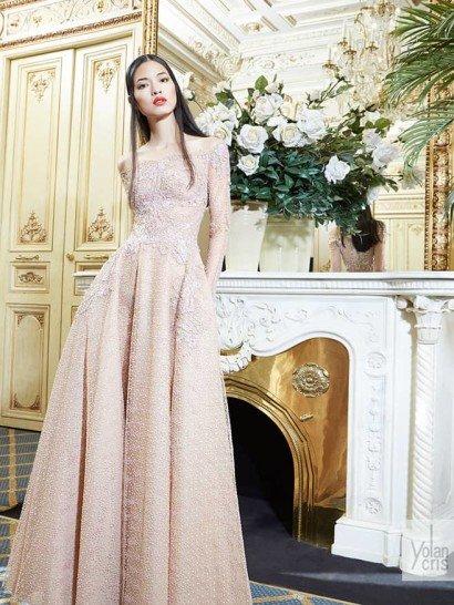 Вечернее платье пастельного розового цвета создано для романтичного образа.  Чувственное портретное декольте, дополненное длинными рукавами прямого кроя, красиво подчеркивает плечи.  Верх декорирован фактурным кружевом, которое покрывает лиф, область талии и спускается вертикальными полосами на подол.  Юбка выполнена из нескольких слоев ткани, верхний из которых выделяется необычной фактурой в мелкий горошек.