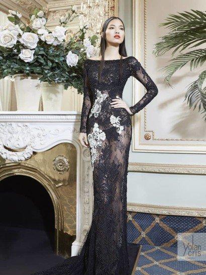 Черное вечернее платье элегантно облегает фигуру прямым кроем.  Закрытый верх с вырезом лодочкой дополняют длинные полупрозрачные рукава с кружевной отделкой по всей длине.  Плотное кружево с объемной фактурой декорирует верх платья, а по полупрозрачной юбке оно спускается в виде аппликаций, вместе с небольшими белыми акцентами.  Сзади юбка образует небольшой ажурный шлейф.