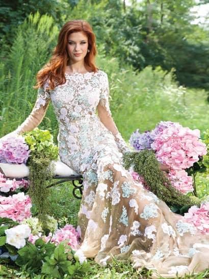 Облегающее вечернее платье создает иллюзию прозрачности ткани - его помогает добиться сочетание полупрозрачного верха бежевого цвета и такой же плотной подкладки в области лифа и от талии до коленей. По всей длине платье покрыто кружевными аппликациями белоснежного и пастельного голубого цветов, которые плотно располагаются от лифа до середины подола и лишь небольшими акцентами - на длинных полупрозрачных рукавах прямого кроя и по нижней части юбки.