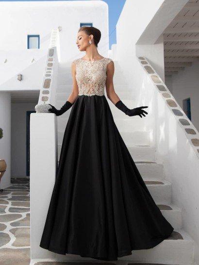 Вечернее платье впечатляет контрастным дизайном с черной юбкой прямого кроя и белым полупрозрачным верхом. Для низа использован глянцевый шелк, а полупрозрачный верх оформлен плотным слоем вышивки из крупных белоснежных бусин и стразов, образующих изысканный узор от стильного выреза лодочкой с широкими бретелями и до самой линии талии, по которой вышивка располагается фигурной полосой.