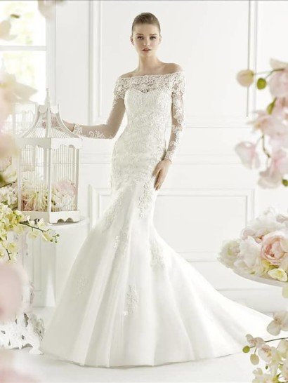 Романтичное свадебное платье с силуэтом «русалка» открывает область декольте нежным лифом в форме сердечка, декорированным по краю объемными матовыми бусинами.  Дополнить его можно кружевным болеро, создающим прямое декольте и длинные облегающие рукава с фигурными запястьями.  Спинку платья декорирует открытая корсетная шнуровка, оформленная атласной лентой, а низ покрывают кружевные аппликации, придающие юбке с небольшим шлейфом сзади роскошную торжественность.