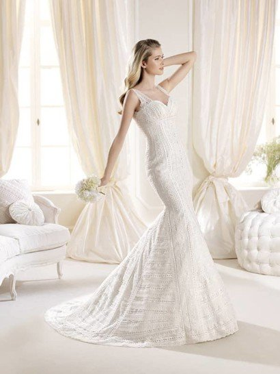 Облегающее фигуру свадебное платье силуэта «русалка» элегантно подчеркивает декольте глубоким вырезом с симметричными бретелями из кружева, обрамляющими его.  По всей длине свадебное платье покрыто такой же кружевной тканью, геометрический рисунок которой подчеркивает очертания силуэта горизонтальными и вертикальными полосами, делая изгибы выразительнее, а шлейф, простирающийся позади, роскошнее.  Завышенную линию талии тоже обозначает узор отделки.