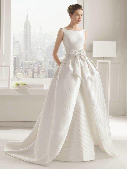 Свадебное платье-трансформер из шелка микадо предоставляет невесте возможность создания двух разных образов.  В каждом из них – верх с широким вырезом-лодочкой, нежно очерчивающий линию плеч, а различия заключаются в нижней части.  Без верхней юбки платье отличается прямым кроем и небольшим шлейфом, а с ней обретает торжественную пышность и романтичное настроение, подчеркнутое крупным бантом пояса на талии.