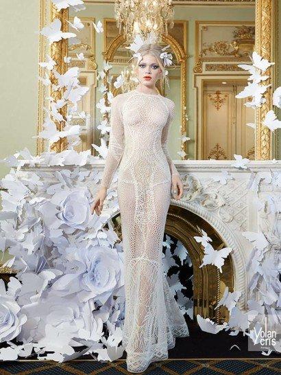 Экстравагантное свадебное платье прямого кроя обрисовывает изгибы силуэта выразительной кружевной тканью, создающей впечатление полной обнаженности, скрытой лишь ажурным узором, напоминающим изысканную паутину.  Соблазнительный образ уравновешен строгим закрытым кроем – высокий вырез под горло, длинные рукава и прямая юбка полностью скрывают фигуру, не делая акцентов на ее особенностях.  Свадебные платья YolanCris эксклюзивно представлены в салоне Виктория  Примерка платьев Yolan Cris—платная