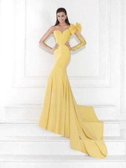 Великолепное вечернее платье теплого желтого цвета облегает фигуру прямым кроем, завершающимся у пола сногсшибательным длинным шлейфом. Соблазнительность образа подчеркивает и глубокое декольте в форме сердечка. Лаконичный декор – платье украшают лишь вертикальные швы, - преображается выше, где от плеча, на котором расположился пышный бант, спускается полупрозрачный ажурный рукав с сияющей вышивкой.