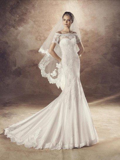 """Чувственное свадебное платье притягивает взгляды не только роскошным облегающим силуэтом """"русалка"""", но и изысканным портретным декольте, оформленным ажурной тканью, которая также создает короткие рукава, спущенные на предплечья.  Кружево покрывает и корсет, спускаясь до середины подола, а ниже юбка приобретает объем и образует выразительные вертикальные складки, сзади складывающиеся торжественным шлейфом."""