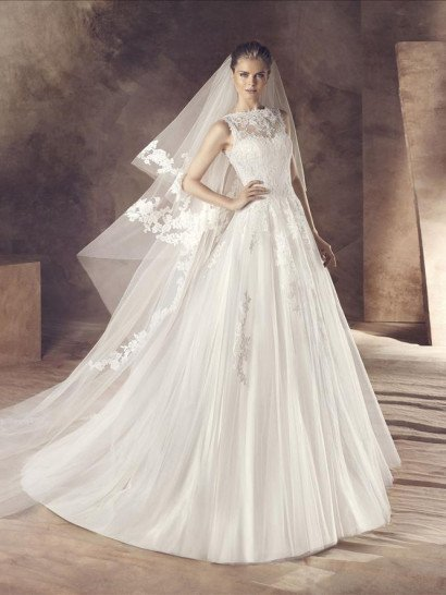 Закрытое свадебное платье стильно обрисовывает фигуру женственным и торжественным А-силуэтом.  Открытый корсет классической формы преображен слоем полупрозрачной ткани, которая закрывает декольте, образуя вырез под горло.  По всей длине ткань декорирована фактурными аппликациями из кружева.  Небольшие глянцевые аппликации украшают и верхний полупрозрачный слой ткани на пышной юбке, декорированной вертикальными складками.