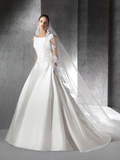 Элегантное свадебное платье с А-силуэтом дополнено оригинальными деталями - скрытыми карманами, роскошным шлейфом, спускающимся почти от самой линии талии, и лаконично декорированным поясом.  Он выделяет талию широкой полосой атласа.  Сдержанный закрытый верх с вырезом лодочкой и широкими симметричными бретелями стильно украшен лишь несколькими вертикальными швами от лифа до талии.  Свадебное платье 2016 года.