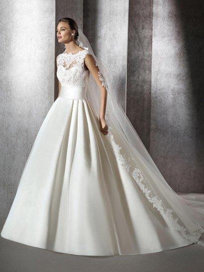 Драматичный и вместе с тем элегантный образ создает закрытое свадебное платье А-силуэта, дополненное роскошным длинным шлейфом.  Открытый лиф в форме сердца укрыт слоем полупрозрачной ткани с крупными кружевными аппликациями по декольте и корсету, а талия смело подчеркнута широким поясом из атласной ткани без отделки.  Спинку платья украшает глубокий округлый вырез, обрамленный кружевной тканью.  Свадебное платье 2016 года.
