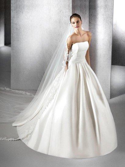 Утонченный и торжественный образ создает открытое свадебное платье из великолепного плотного атласа.  Подчеркнуть лаконичную красоту кроя помогает сдержанная линия декольте.  Акцентом в силуэте служит изящный широкий пояс, декорированный горизонтальными драпировками ткани.  От талии спускаются пышные складки ткани, вертикальными волнами украшающие подол роскошной юбки с небольшим полукругом шлейфа сзади.
