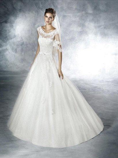 Потрясающее свадебное платье 2016 года с легким намеком на винтажный стиль. Он выражается в женственной форме выреза-лодочки и в сочетании А-силуэта юбки с акцентом на талию в виде тонкого пояса с кокетливым бантом.  Благодаря небольшому шлейфу и использованию для верха платья полупрозрачной ткани образ становится роскошнее. Декор выполнен из кружевных аппликаций с белыми пайетками и украшает как лиф, так и подол свадебного платья.  Это белое вечернее платье можно использовать в качестве свадебного!