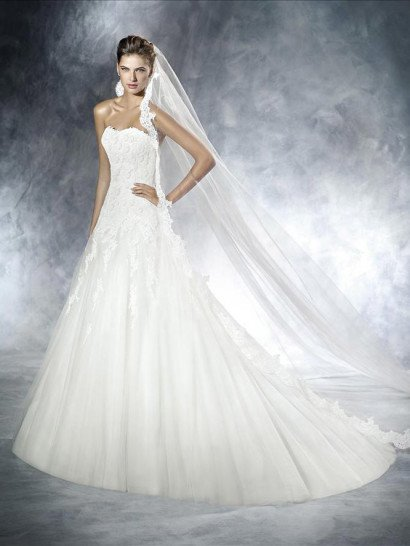 Роскошное свадебное платье со съемным кружевным болеро позволяет создать сразу два потрясающих образа.  Юбка А-силуэта, начинающаяся от заниженной линии талии, выразительно воплощается в нескольких слоях матового тюльмарина, сзади образующих объемный шлейф.  Верхняя часть платья притягивает внимание не только оригинальным кружевным аксессуаром, но и самой фактурой ткани.  Плотная отделка покрывает открытый лиф сердечком и область декольте, фигурно спускаясь на юбку.