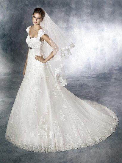 Романтичное недорогоекружевное свадебное платье А-силуэта.  Линия талии завышена и подчёркнута атласным пояском, украшенным под грудью крупной брошью, инкрустированной бисером, стеклярусом, кристаллами.  Фигурная линия фестонов рукавов-крылышек и верхнего края лифа эффектно обрамляют зону декольте и вырез на спине.  Сзади – застёжка-молния, закрытая цепочкой пуговиц.  Свадебное платье от Pronovias Fashion Group
