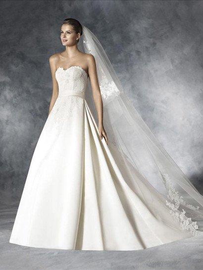 Открытое свадебное платье позволяет соединить в одном образе сдержанную элегантность и торжественную роскошь.  Корсет с соблазнительным лифом в форме сердечка покрыт кружевной тканью с мелким цветочным рисунком.  На кружеве выразительно выделяется глянцевая атласная фактура узкого пояса, подчеркивающего естественную линию талии.  Изысканная пышная юбка украшена вертикальными складками ткани и полукругом шлейфа.