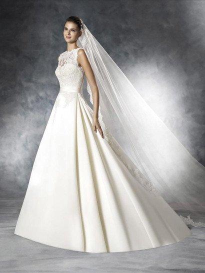 Подчеркнуть утонченный стиль невесты поможет закрытое свадебное платье с А-силуэтом.  Оно безупречно подчеркивает фигуру благодаря широкому атласному поясу на талии и облегающему корсету, а также создает атмосферу нежности фактурным кружевом, скрывающим лиф в форме сердечка спереди и обрамляющим изысканный глубокий V-образный вырез сзади, на спинке свадебного платья.  Роскошная юбка дополнена небольшим шлейфом.