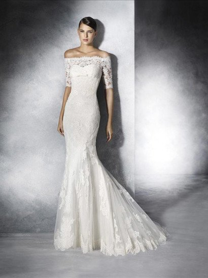 """Оригинальное портретное декольте в сочетании с облегающим силуэтом """"русалка"""" это идеальная комбинация, позволяющая свадебному платью безупречно подчеркивать изящную фигуру невесты.  По всей длине свадебное платье декорировано фактурной кружевной тканью с мелким плотным рисунком.  Завышенная линия талии выделена узким атласным поясом, украшенным спереди бантом, а спинку декорирует вертикальный ряд пуговиц."""