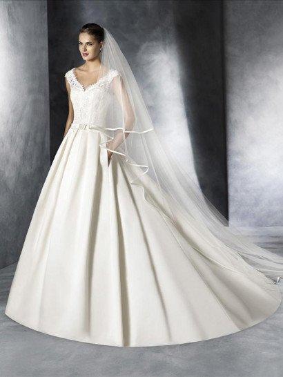Образ в изысканном классическом стиле создаст свадебное платье А-силуэта, по всему верху декорированное кружевом.  Ажурный узор скрывает открытый лиф, создавая небольшой V-образный вырез и широкие бретели, а также декорирует глубокий округлый вырез на спинке свадебного платья.  Талия выделена узким поясом с небольшим бантом спереди, а юбку украшают вертикальные драпировки и потрясающий пышный шлейф, кроме того, она дополнена скрытыми карманами.  Свадебные платья White Oneэксклюзивно представлены в салоне Виктория