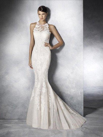 """Облегающее свадебное платье с силуэтом """"русалка"""" по всей длине выразительно декорировано кружевными аппликациями с крупным рисунком.  Они не только придают дополнительный объем соблазнительной юбке и украшают корсет, но и покрывают полупрозрачную фактурную вставку, располагающуюся над лифом в форме сердечка.  На спинке женственного свадебного платья располагается большое декольте """"замочная скважина"""", обрамленное кружевом."""