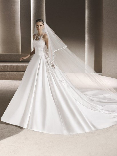 Невероятно торжественное и безупречно элегантное свадебное платье сразу же покоряет пышной юбкой, простирающейся длинным шлейфом.  Открытый верх с лифом в форме сердечка покрыт тонким слоем ткани, декорированной кружевными аппликациями, она скрывает область декольте и украшает открытую спинку сзади.  Стильно подчеркнуть область талии помогает широкий атласный пояс, декорированный горизонтальными складками ткани.