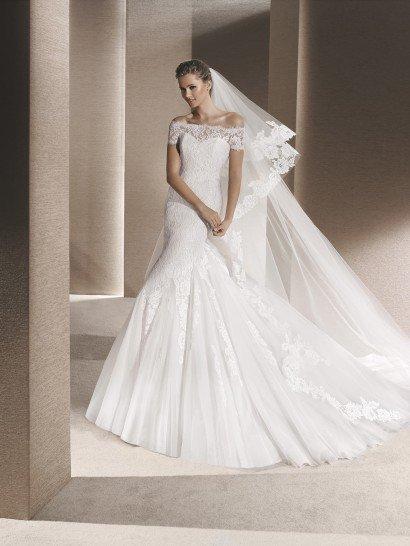 """Романтичное свадебное платье с привлекательным силуэтом """"русалка"""" идеально подчеркнет фигуру невесты и позволит продемонстрировать ее безупречное чувство стиля изящным портретным декольте, оформленным кружевной тканью, которая создает и широкие бретели, спущенные на предплечья.  Кружево покрывает и корсет, а также располагается аппликациями по многослойной юбке, которая становится пышной ниже уровня коленей."""