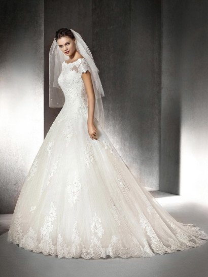 Свадебное платье с небольшим рукавом и вырезом-лодочкой позволяет продемонстрировать всю красоту шеи и плеч.  Отделка крупным кружевом украшает линию верха, а корсаж расшит декоративными жемчужинками.  Спину свадебного платья украшает ряд сияющих пуговиц.  Объемная юбка выполнена из нескольких слоев легкого, полупрозрачного материала и украшена кружевной аппликацией по всей длине и по нижнему краю.