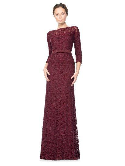 Элегантное вечернее платье прямого силуэта впечатляет насыщенным оттенком ткани – темный бордовый цвет прекрасно дополняет выразительный рисунок плотного кружева, покрывающего платье по всей длине.  Ажурная ткань не просто придает фактуру подкладке, но и образует вставку в области декольте и создает короткую баску, спускающуюся от выделенной широким лаконичным поясом с небольшим бантом талию.  Есть платья больших размеров.